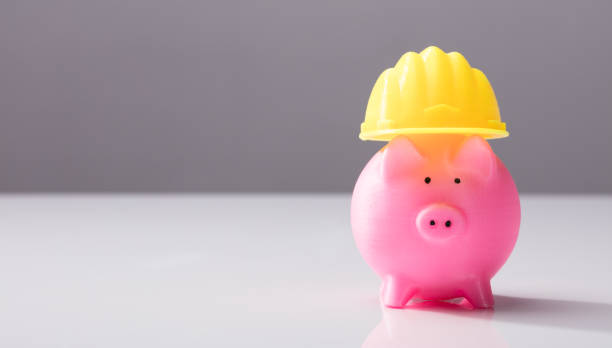 Close-up Of A Piggy Bank With Hard Hat Close-up Of A Pink Piggy Bank With Yellow Hard Hat On White Desk 40 kilometre stock pictures, royalty-free photos & images