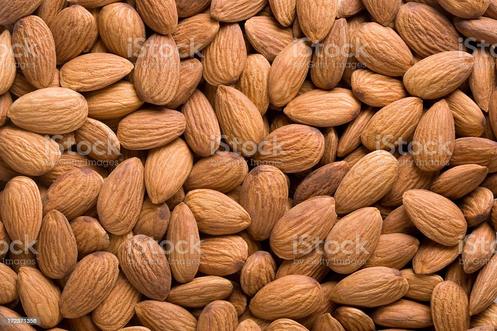 A closeup of a pile of raw almonds stock photo