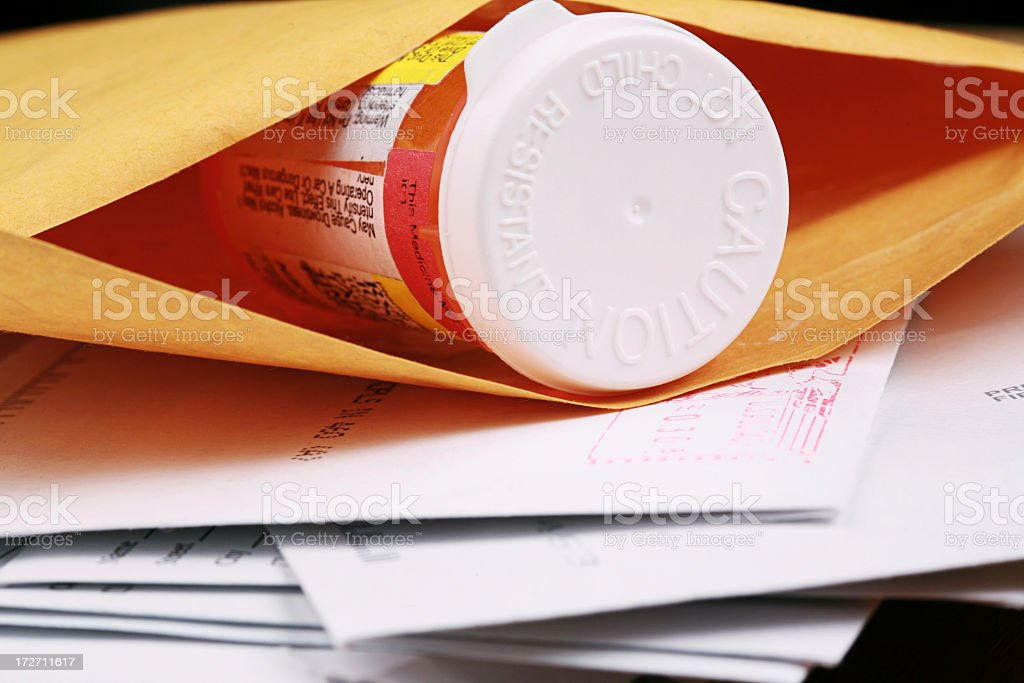 A close-up of a pill bottle in an envelope stock photo