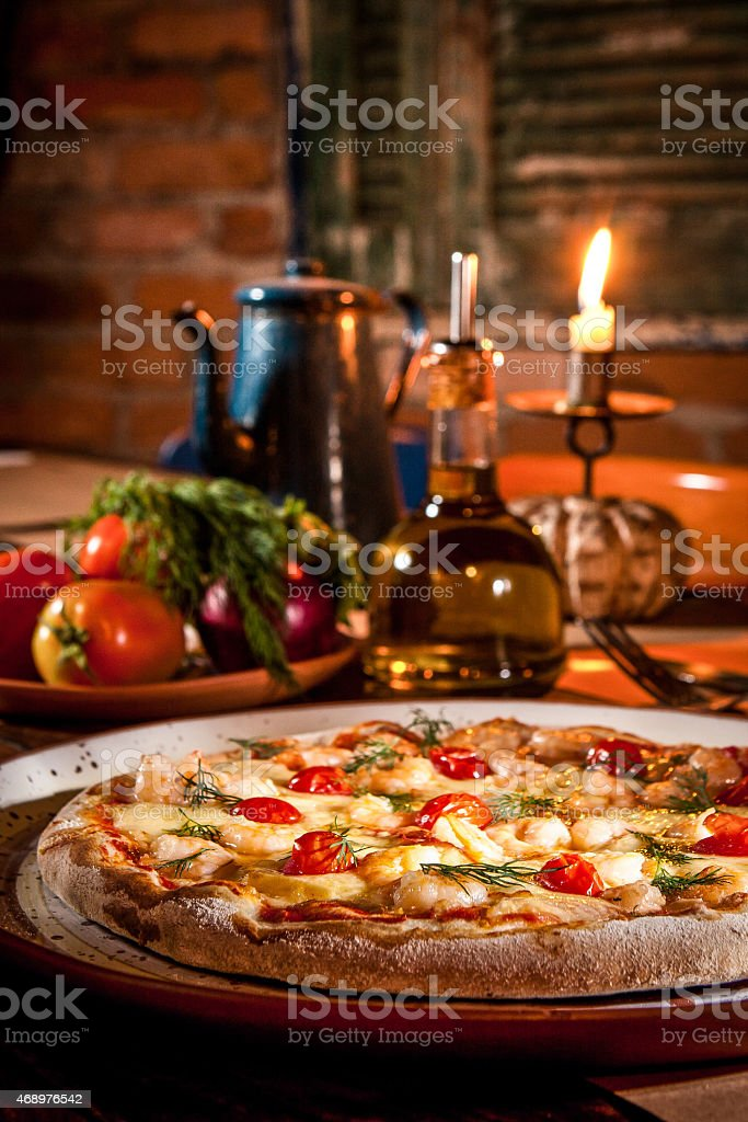 Close-up of a pizza on a tray next to jug of oil and candle stock photo