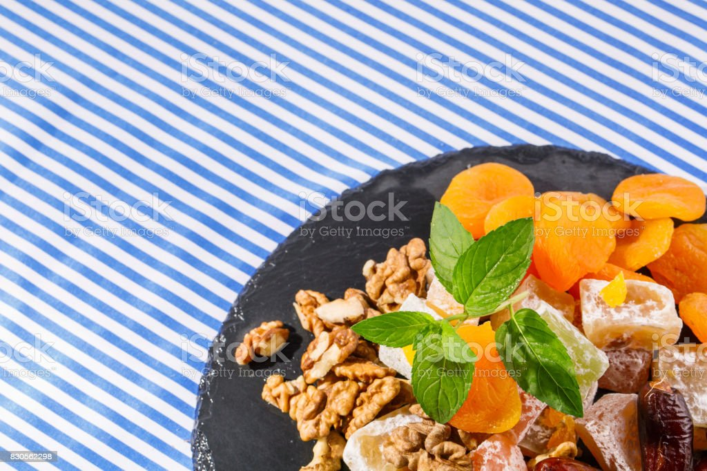 Closeup of a plate with rahat lokum, sweet date fruits, dry apricots, walnuts and leaves of mint on a striped background stock photo