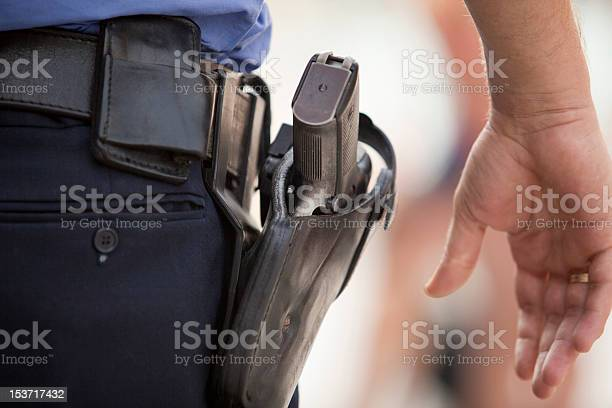A policeman with his hand close to his gun.