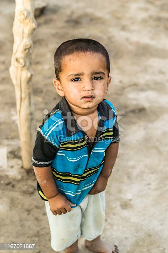 istock closeup of a poor staring hungry orphan boy in a refugee camp with sad expression on his face and his face and clothes are dirty and his eyes are full of pain 1167021667