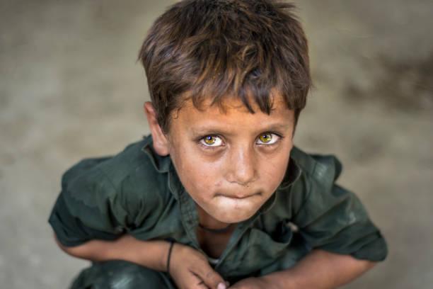närbild av en fattig stirrade hungrig föräldralös pojke i ett flyktingläger med sorgliga uttryck på hans ansikte och hans ansikte och kläder är smutsiga och hans ögon är fulla av smärta - dirty money bildbanksfoton och bilder