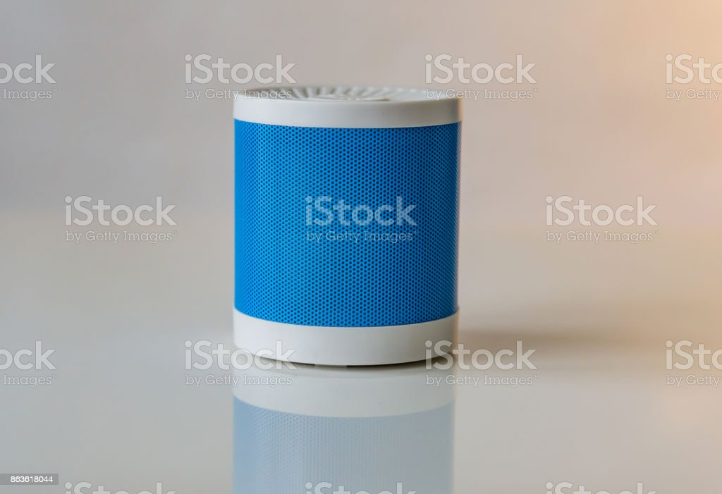 Close-up of a portable speaker on a white background connecting to a smartphone. Concept Technology. stock photo