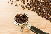 Portafilter, filter holder, of a professional espresso machine filled with freshly roasted coffee beans. In the background coffee beans spread out on a light brown wooden background. Selective focus, shallow depth of field and backlit.