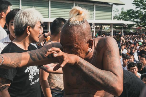 eine nahaufnahme von einem besessenen mann während des wai kru festivals bei dem wat bang phra - buddhist tattoos stock-fotos und bilder