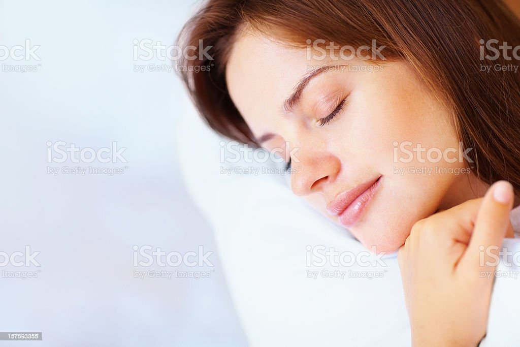 Closeup of a pretty female fast asleep in bed stock photo