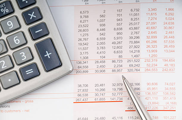 Close-up of a print out of a balance sheet with calculator close up photo of statement with figures in British pounds bank statement stock pictures, royalty-free photos & images