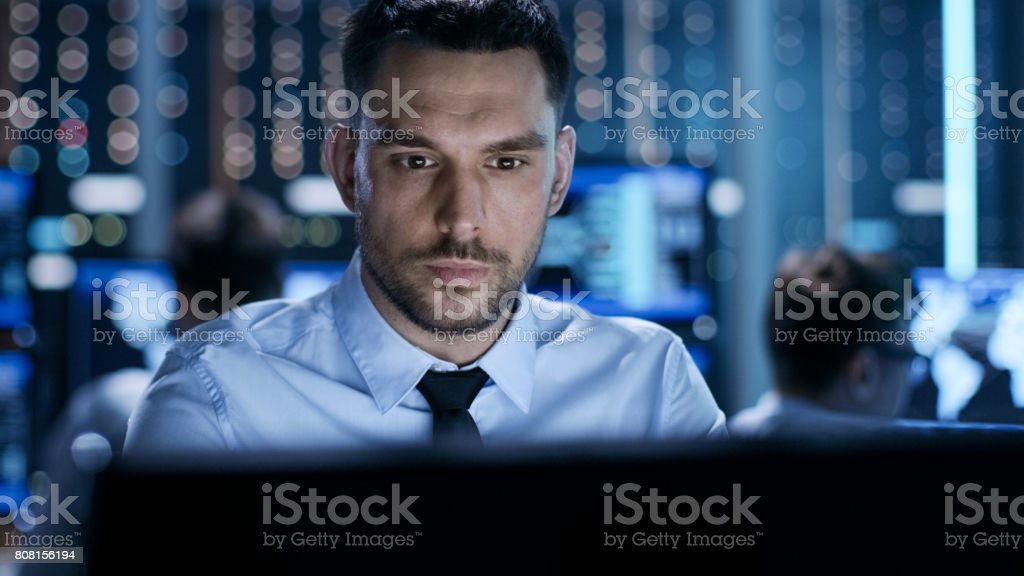 Close-up of a Professional Technical Controller Sitting at His Desk with Multiple Displays Before Him. In the Background His Colleagues Working in System Control Center. - Royalty-free Adult Stock Photo