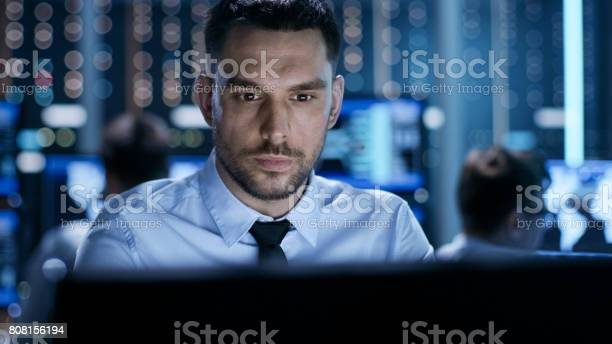 Closeup Of A Professional Technical Controller Sitting At His Desk With Multiple Displays Before Him In The Background His Colleagues Working In System Control Center Stock Photo - Download Image Now