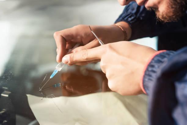 nahaufnahme eines professionellen windschutzgerätes füllt einen riss im glas mit einem speziellen polymer durch eine spritze. beseitigung von rissen und chips auf windschutzscheiben - fensterbauer stock-fotos und bilder