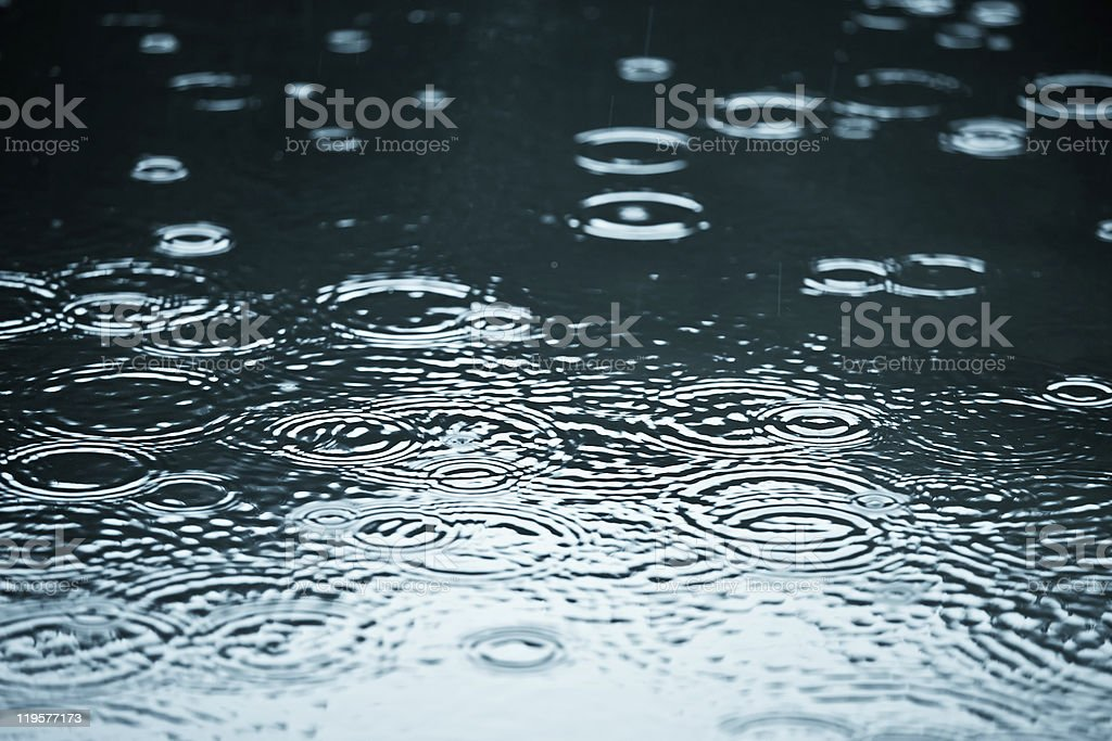 Close-up of a puddle with rain drop ripples stock photo