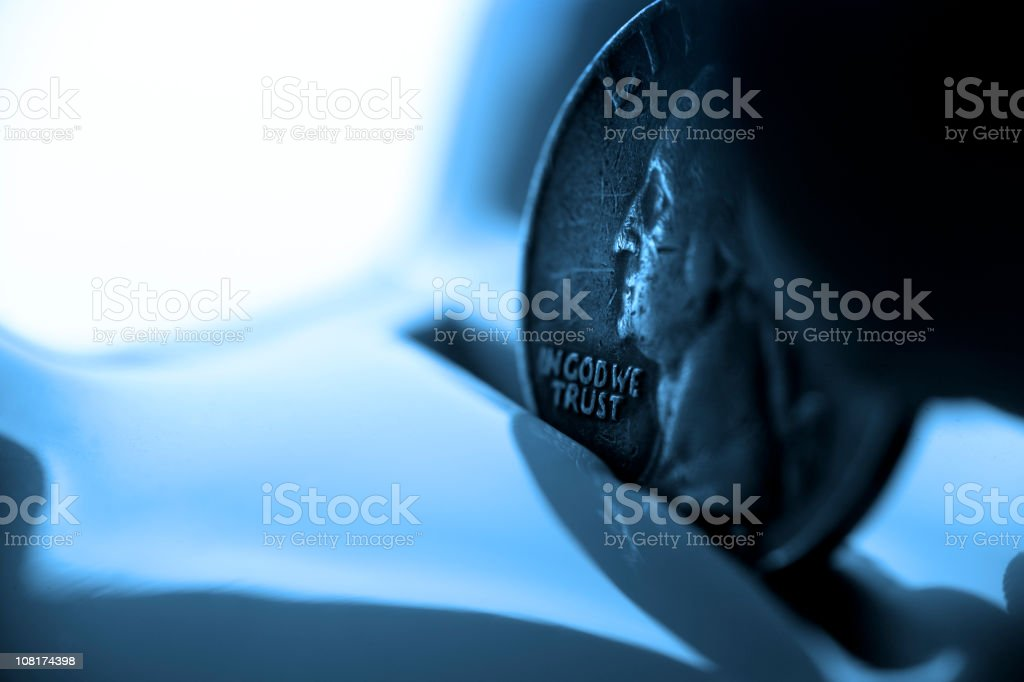 Close-up of a Quarter Coin Being Dropped Into Piggy Bank royalty-free stock photo