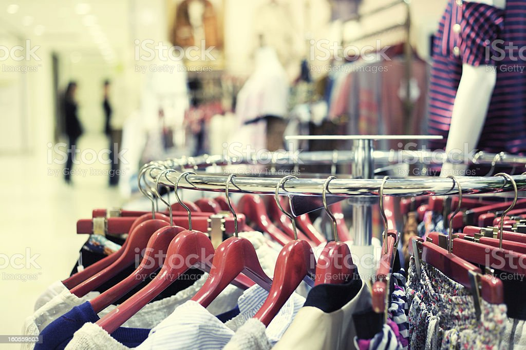 Close-up of a rack of clothes with clothes in red hangers stock photo