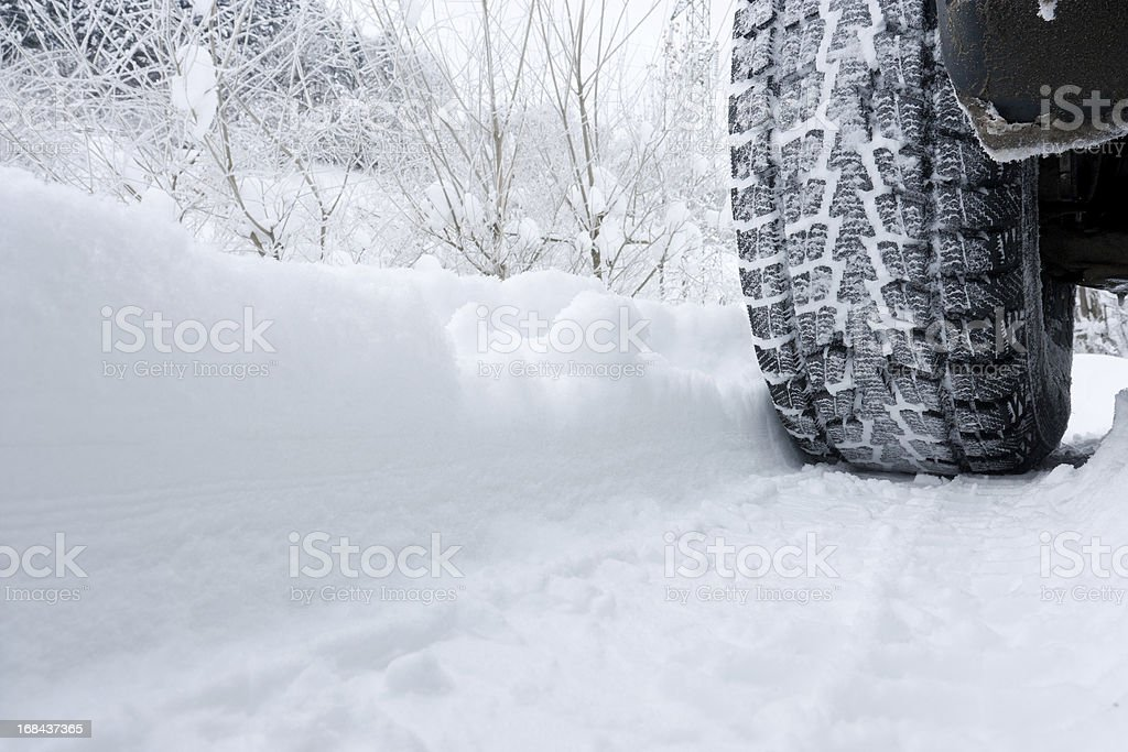 Close-up of a rear black tire in the snow creating tracks stock photo