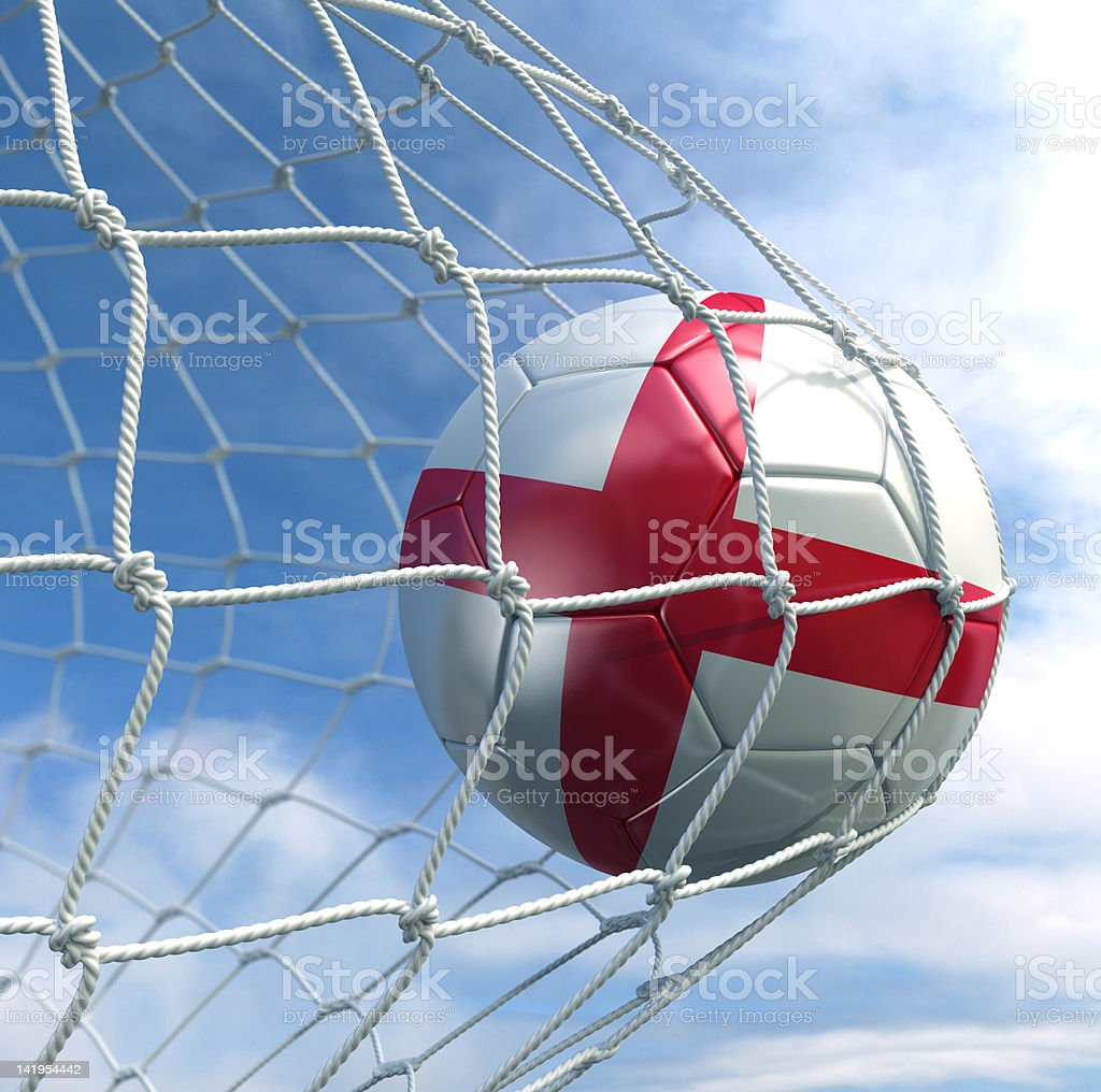 Close-up of a red and white soccer ball hitting the net stock photo