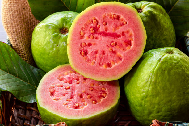 Closeup of a red guava cut in half, in the background several guavas and green leaf. Closeup of a red guava cut in half, in the background several guavas and green leaf guava stock pictures, royalty-free photos & images