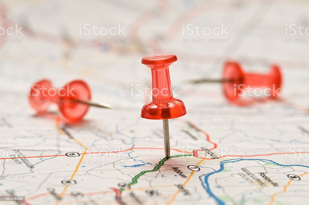 Close-up of a Red pushpin stuck into a map stock photo