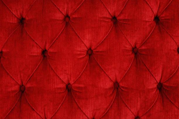 nahaufnahme eines roten gesteppten samt sofa mit rot gepolstert tasten (diamant nähte) / rautenheftung - stuhlpolster stock-fotos und bilder