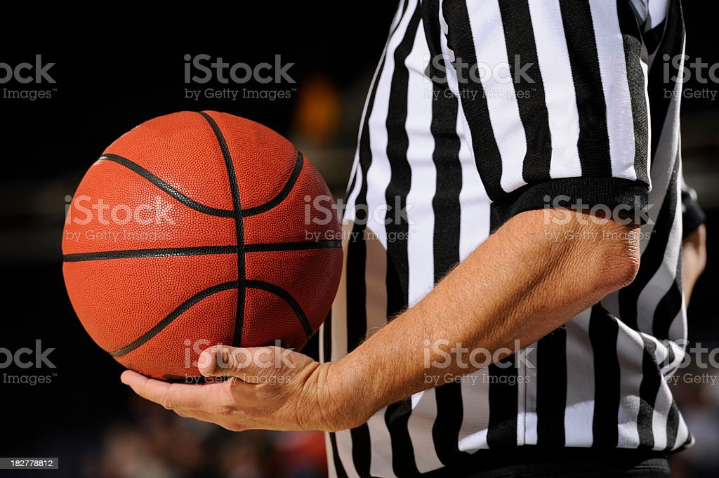 A close-up of a referee holding a standard basketball royalty-free stock photo