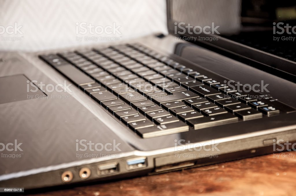 A closeup of a right side of a notebook keyboard and part of a screen with focus on a number panel stock photo