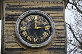 Close-up of a round clock face in a wooden tower with peeling paint and gold coloured clock hands and roman numerals in Kent, England, UK.