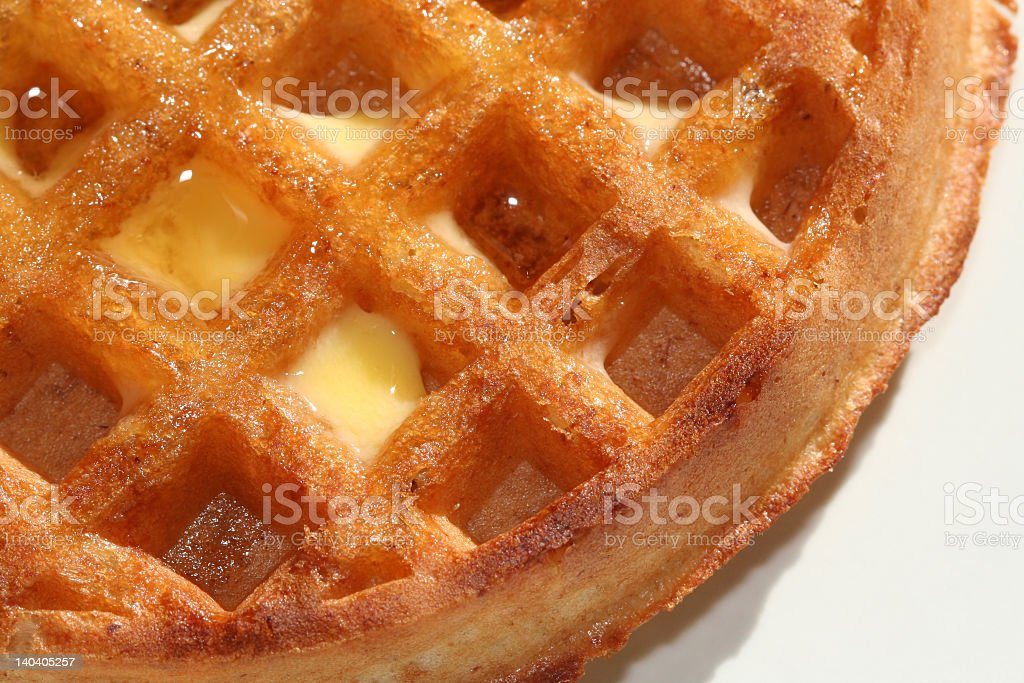 Close-up of a round waffle with butter and maple syrup royalty-free stock photo