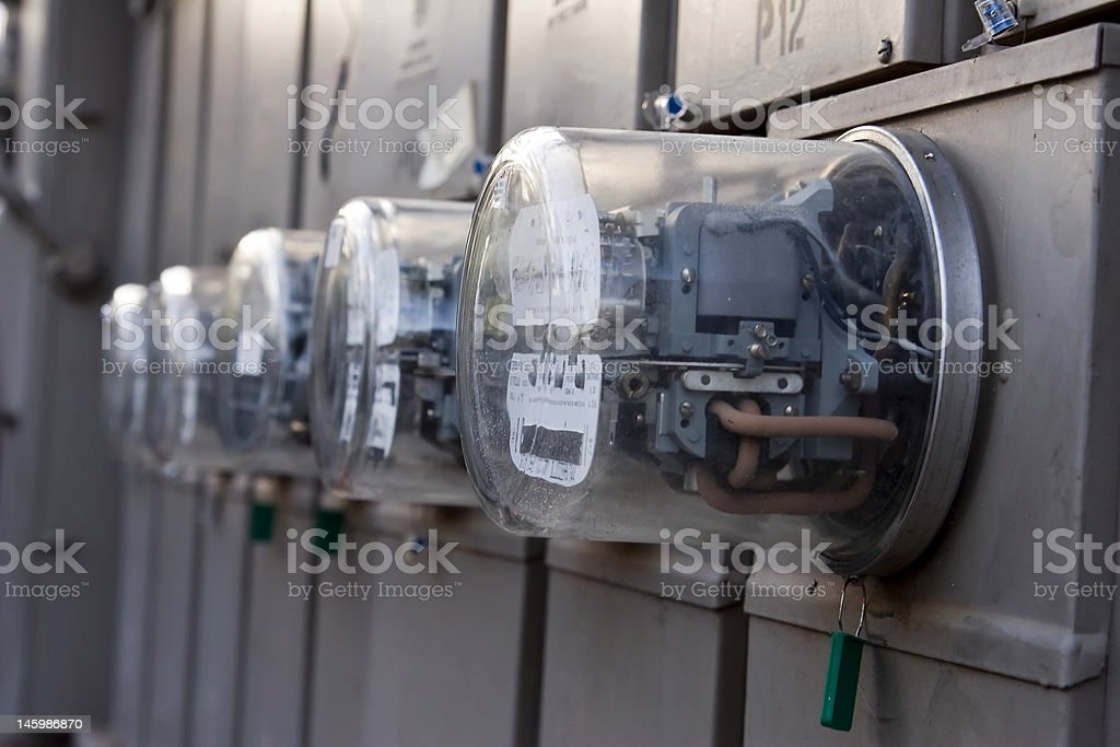 Close-up of a row of outdoor mounted electrical meters stock photo