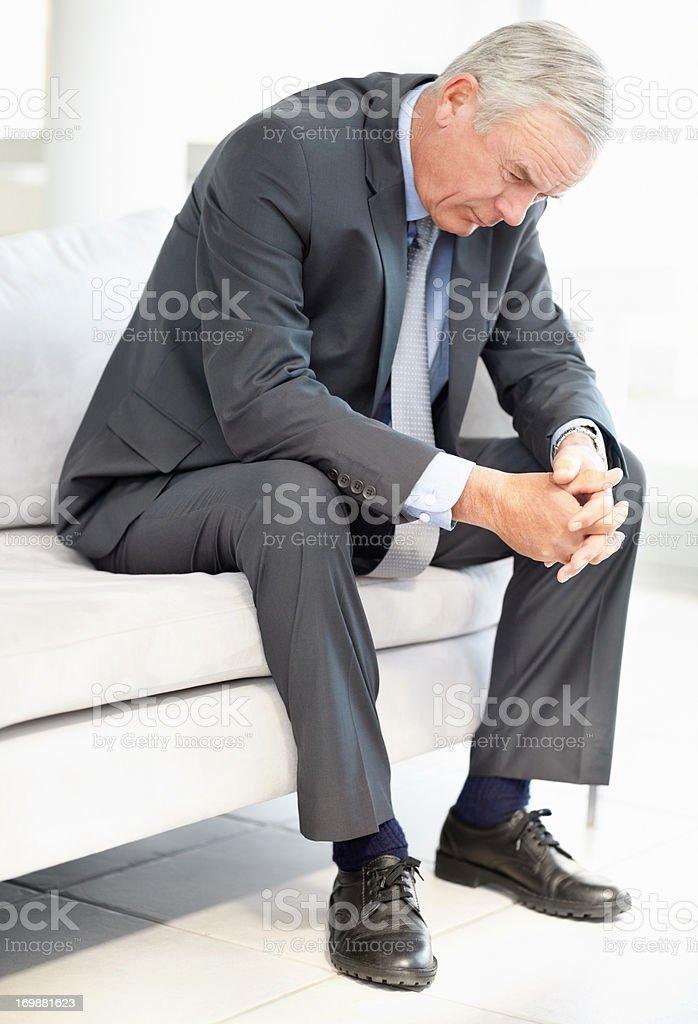 Nahaufnahme von eine traurig Geschäftsmann sitzt auf sofa – Foto