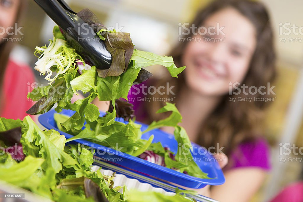 Closeup of a salad being served to school students stock photo