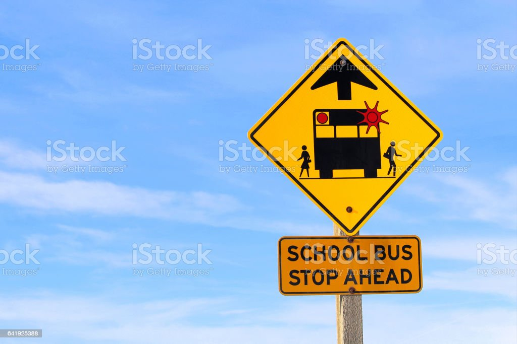 Closeup of a School Bus Stop Ahead Sign Against a Blue Sky stock photo