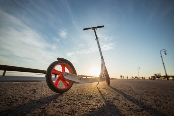 Close-up of a scooter on the asphalt. White kick scooter with orange wheels.. Sport activity on summer sunset stock photo