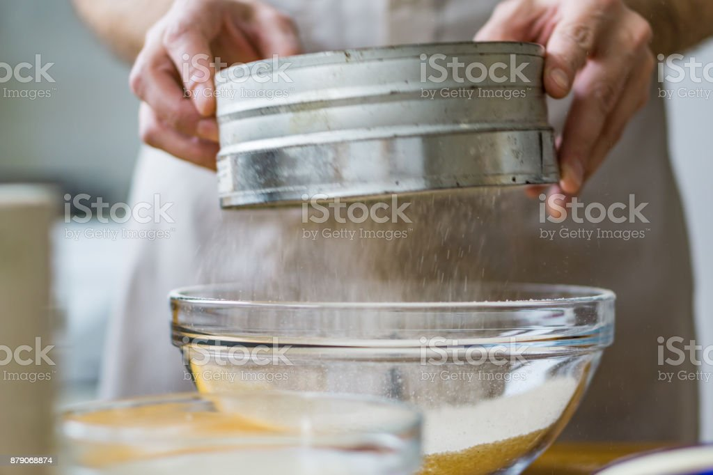 Close-up of a screening sieve for preparing a Christmas cake. Shallow depth of focus. stock photo