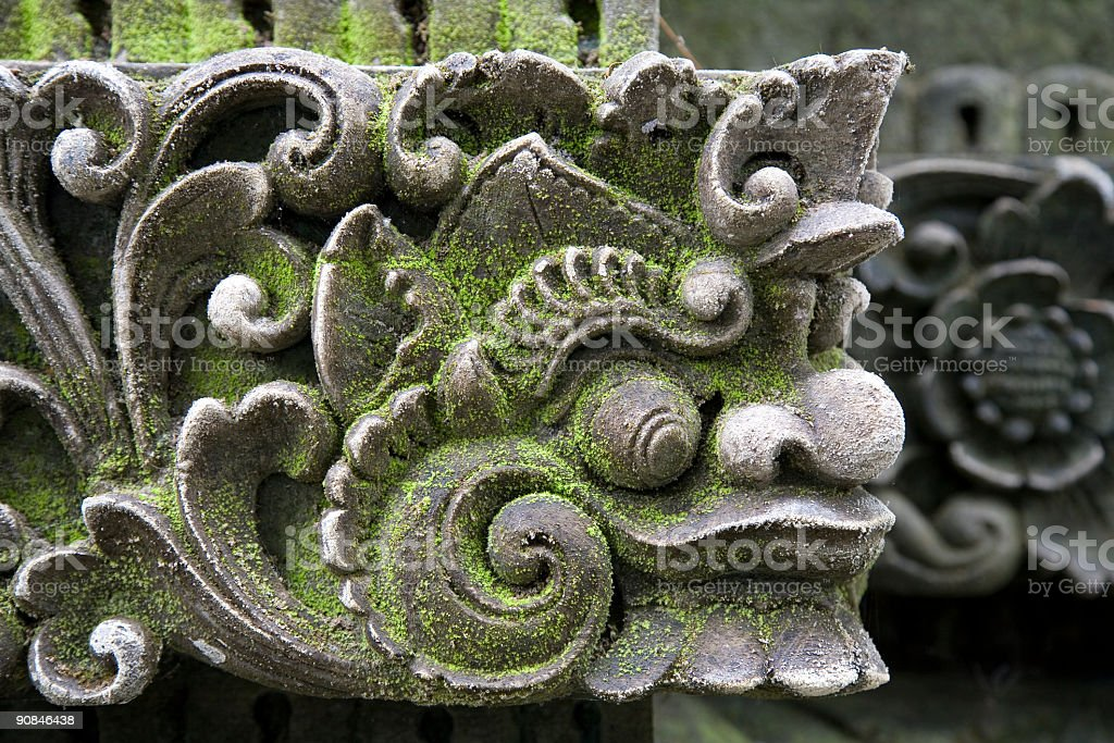 Close-up of a sculpture's head with moss in a temple royalty-free stock photo