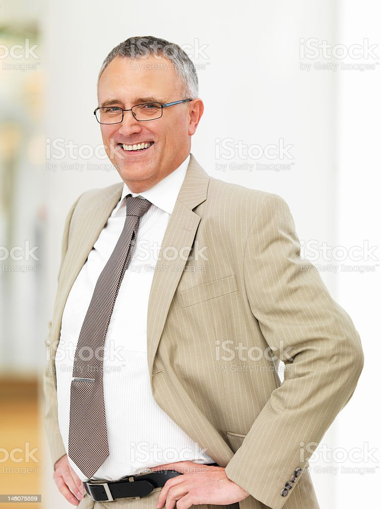 Close-up of a senior businessman standing with hands on hips royalty-free stock photo