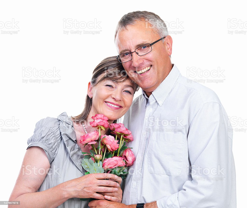 Close-up of a senior couple holding flowers against white background royalty-free stock photo