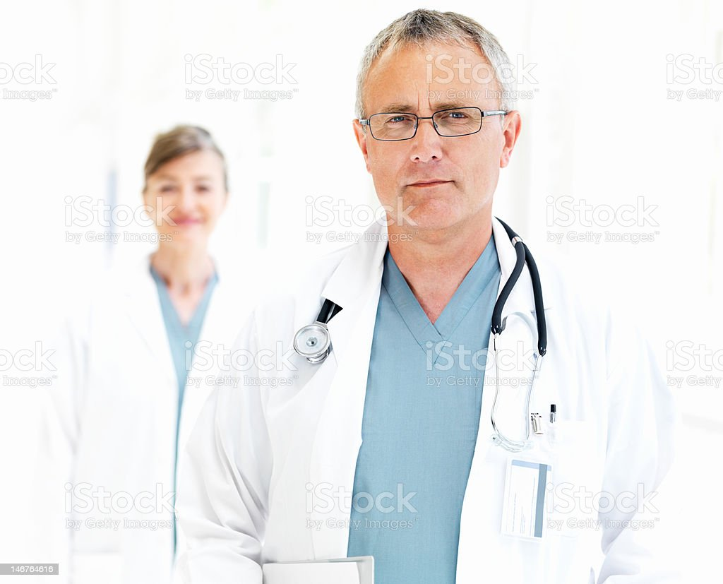 Close-up of a senior doctor with nurse in the background royalty-free stock photo