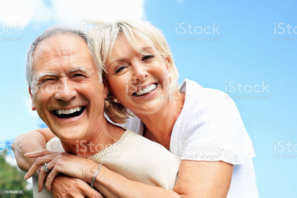 Close-up of a senior man piggybacking his wife against sky royalty-free stock photo
