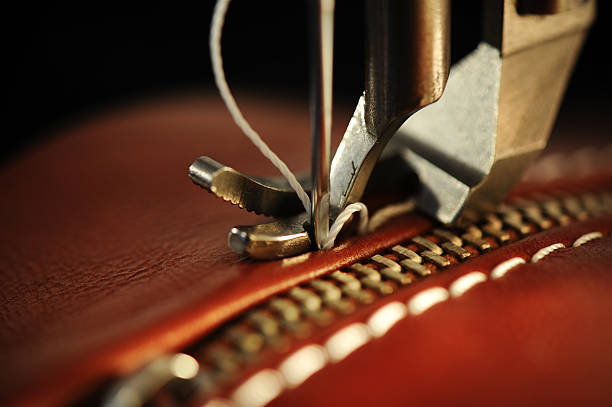 close-up of a sewing machine with needle on red leather - sewing machine needle stock photos and pictures