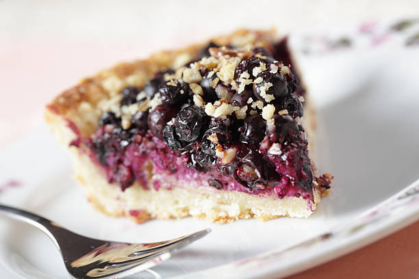 close-up of a slice of blueberry pie on a white plate - blueberry pie stock pictures, royalty-free photos & images