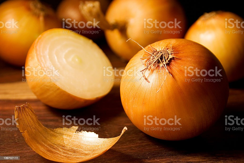 Close-up of a sliced onion and several full onions stock photo