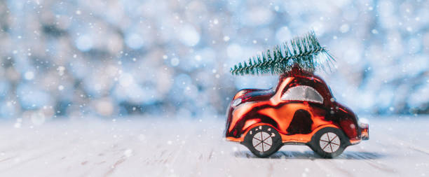 Close-up of a small toy car carries a xmas tree on the roof stock photo
