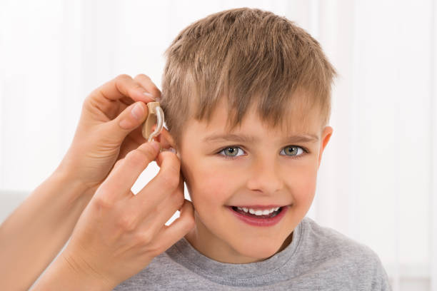 Close-up Of A Smiling Boy With Hearing Aid stock photo