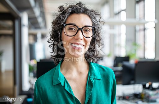 Close-up portrait of smiling mid adult businesswoman standing in office. Woman entrepreneur looking at camera and smiling
