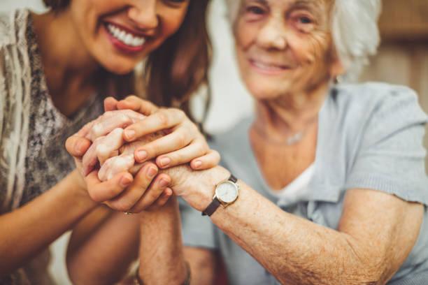 nahaufnahme einer lächelnden krankenschwester, die die hand einer seniorin hält - erinnerung stock-fotos und bilder