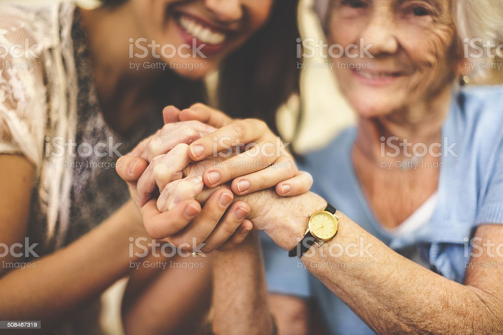 Close-up of a smiling nurse holding a senior woman's hand royalty-free stock photo
