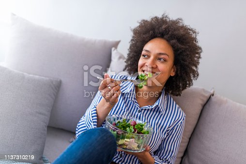 Close-up of a smiling woman eating a salad in the living-room. Beautiful African American Woman Eating Salad At Home. Nice joyful woman eating salad