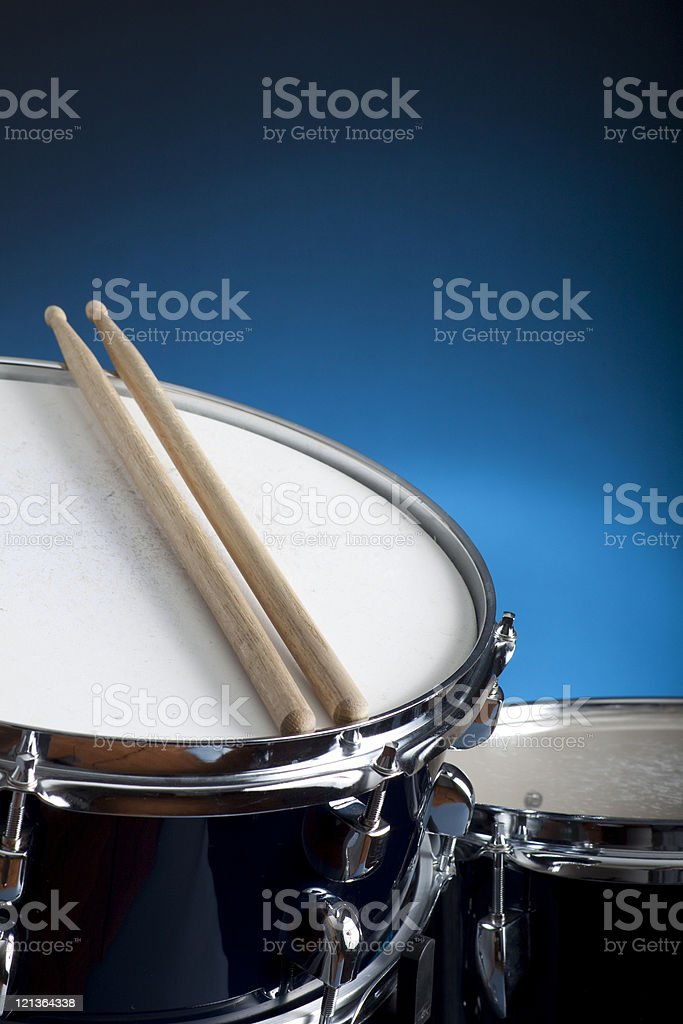 Close-up of a snare drum with two drumsticks and blue wall stock photo