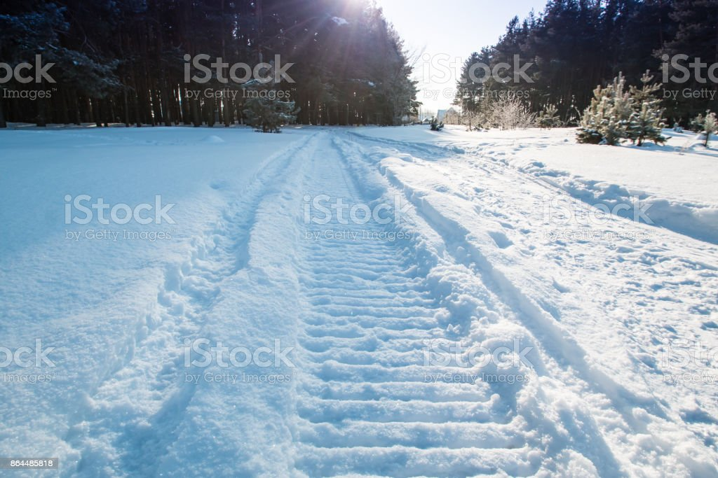 Close-up of a snowmobile trace on snow and sun stock photo